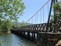 """Bidwell Bar Suspension Bridge (at high water mark) - This structure is the only surviving suspension bridge in the American West dating to the mid 19th century.  Originally built over the Feather River in 1856, it was closed in 1954.  It was relocated over Lake Oroville in Butte County, CA, in 1967 and """"strengthened"""" with pile supports under the bridge deck.  It is now a pedestrian bridge.  - photo by Larry Matthews"""