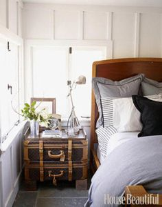 Two mostly black vintage Louis Vuitton suitcases propped on wood blocks and topped with a tray serve as a night table in this master bedroom designed by Ken Fulk. The bedding is black-and-white with stripes and plaid.