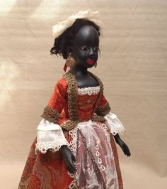 "Matilda 17 1/2 "" tall black Queen Anne doll. Carved from wood, full jointed, antique glass eyes, doll wig made from natural lamb skin. All antique textiles.Woven wool fabric, velvet, lace ,metallic trims, all saved from antique costumes, Matilda has tiny bag and velvet pincushion. 