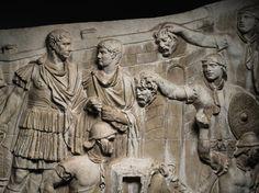Detalhe da coluna de Trajano Trajano assiste a uma batalha e duas auxiliares os oferecem as cabeças decapitadas dos inimigos.