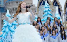 Lexi Walker Photos Photos - In this handout photo provided by Disney Parks, Lexi Walker performs 'Let It Go' during the taping of the Disney Parks 'Frozen Christmas Celebration' TV Special in the Magic Kingdom Park at the Walt Disney World Resort on December 8, 2014 in Lake Buena Vista, Florida. The special will air on December 25, 2014. - 'Frozen' Christmas Celebration TV Special