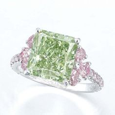 AN EXCEPTIONAL COLOURED DIAMOND RING, BY MOUSSAIEFF. Set with a rectangular-shaped fancy intense green diamond weighing approximately 5.02 carats, flanked by pear-shaped pink diamonds, to the brilliant-cut pink diamond gallery and three quarter-hoop, mounted in platinum, ring size 5¾, in black suede Moussaieff case Signed Moussaieff
