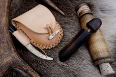 Handmade pouch in natural blonde leather with handmade antler toggle, handmade fire steel with Antler handle, handmade wooden Hobo reel and handmade wooden Fire Piston, all at Beaver Bushcraft