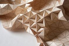 "German designer Elisa Strozyk's Miss Maple lamp is made out of hundreds of wooden triangles that she has transformed into a flexible textile. Normally one thinks of wood as simply a hard material but she has created a material that she calls Wooden Textiles that are ""half wood-half textile."" Even though this piece is made essentially from wood, it still remains delicate and sculptural. The spaces between the triangles emit a warm glow from the light inside."