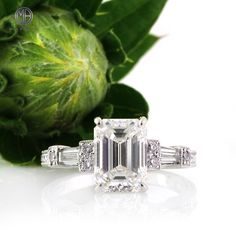 his mesmerizing vintage inspired emerald cut diamond engagement ring will captivate you with its beauty. The stunning 2.36ct emerald cut center diamond is GIA certified at H-VVS1. It is white, practically flawless, and it has an exceptional cut!