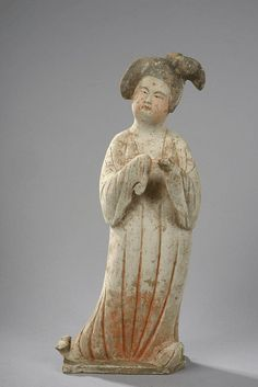 Princess with buxom standing with hands folded, wearing a long pleated dress and wearing a high bun. Terracotta to slip and polychrome. China. Tang Dynasty. 618-907. 48cm H