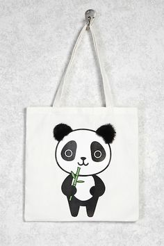 A canvas woven tote bag featuring a front panda graphic with faux fur ears, as well as dual shoulder straps.