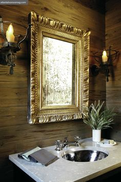 """""""I love the way Nancy Warren contrasted the old farmhouse feel with the gilded gold mirror,"""" says Dixon of the cypress-paneled powder room with torch-like sconces."""
