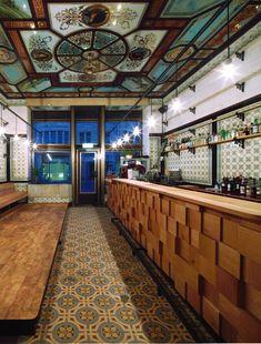 Le comptoir en bois apporte la note contemporaine dans ce magnifique décor 19ème.  michael grzesiak transforms a century old butcher shop into a bar