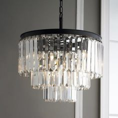 "Sleek angled prisms dangle from a bronze iron frame in 3 tiers for layers of sparkling style. The blend of rounded forged bronze hardware adorned with five sided clear glass crystals has an allure of restoration era luxury for interiors ranging from industrial to glamorous. 9 x 40 watts max, (candle base socket). Hardwire only. (Crystal body 15.5""H x 20""W). (23"" minimum installed height x 20"" diameter). 4' of chain. 4.75"" canopy. 37 lbs. Assembly required. Suppl..."
