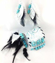 """8"""" x 3"""" white and turquoise embossed leather cuff with turquoise gemstones, silver finish square beads, black and white feathers, black leather string accents; stretch enclosure; 4"""" earrings, silver finish clasp hooks  Item EB 146    $40.00 www.ndjdesigns.com"""