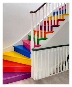 Colorful Indoor Rainbow Staircase, set in contrast to white walls and white with wood trim bannister