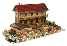 Noah's Ark on Wheels, Wooden & Figures, German, Late 1800's. Arc on four metal spoked wheels with balcony to first floor. Body is painted in a mixture of yellow, red, mushroom and black with printed paper, coloured tiles to the top. Roof lifts to reveal a stabling area for the menagerie of animals featuring leopards, camels, elephants and deer, in total 40 pairs and 25 singles.