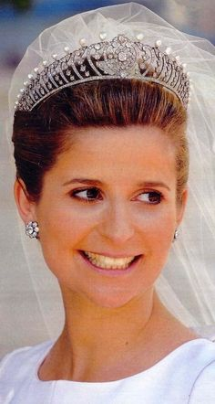 A beautiful belle epoque tiara, circa 1900. Worn by Diane, Duchess of Cadaval, Portugal, when she married Prince Charles-Phillippe, Duke of Anjou. The tiara is designed as a series of diamond scrolls, each topped with a button pearl, with a central diamond cluster.