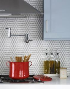 A backsplash of white hex tiles in an Atlanta kitchen by TerraCotta.