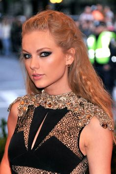T-Swift knows just how to emphasize her bold eye makeup with this tousled twist on the traditional half up/half down hairstyle.   - MarieClaire.com