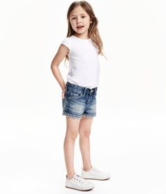 5-pocket shorts in washed denim with distressed details. Adjustable elasticized waistband, zip fly with snap fastener, and embroidered, scalloped hems.