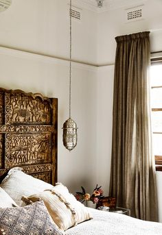 An intricate, hand-carved bedhead from Shikara Design in Byron Bay is the crowning glory of the master bedroom. Neutral-coloured bedlinen from restoration hardware. The Moroccan pendant light is from Ha'veli.