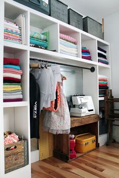 cubbies of fabric surround a metal board so patterns, ideas can be magnet-ed onto it.  Pipe holds almost finished projects, patterns clipped and hung with skirt hangers.  Neat.
