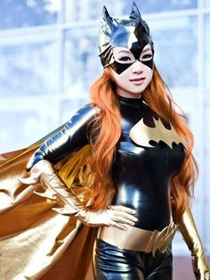 Cosplayer wears sexy black and gold Batwoman costume made from stretch PVC, complete with cape, belt and mask.. DIY the look yourself: http://mjtrends.com/pins.php?name=stretch-pvc-material-cosplay