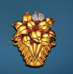 A diamond and ruby clip brooch, circa 1950  The mount composed of a stylised basket of overlapping leaves, one pavé-set with brilliant-cut diamonds, set at intervals with circular cabochon rubies, length 6.8cm. [Borderline fugly, but nevertheless, part of the fifties aesthetic.]