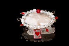 Clear Quartz beads with an array of charms in card suits, red Swarovski crystal pave bead.Quartz is a common stone, but a powerful one. It is mainly used in healing as amplification for the energies of the other working stones.This is a stretch bracelet and will fit any average size wrist.
