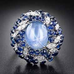 Vintage Star Sapphire Cocktail Ring,An enchanting 8 carat sky-blue star sapphire, displaying a billowy six-legged star, glows from the center of a big bombe-shape bauble crafted in 18 karat white gold - circa 1960s.