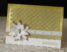 Shiny gold fancy lattice over dull gold card, layered on ivory. Handmade ivory poinsettia, gold heat embossed edges.
