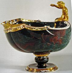 The young Bacchus shell cup made by Ottavio Miseroni around 1605 (19cm high, 19cm long and 17cm wide) in green red agate from Kozakov with enamelled gold mounting and lip by Jan Vermeyen. The boy in gold has a green leaf crown and was once holding a fishing rod in his right hand. It is attributed also to Ottavio. From the collection of Rudolf II and now in the KHM in Vienna