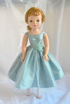 Close-up of aqua silk party dress on vintage Cissy