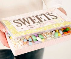 Make a personalized candy stash using the recipient's favorite candies, a plastic divided box, and scrapbook paper.