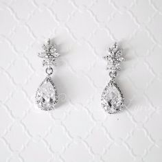 Teardrop cubic zirconia stones that are surrounded by many smaller stones dangle from marquise CZ flowers in these classic yet radiant CZ earrings set in rhodium silver. They are about 1.25 inches lon