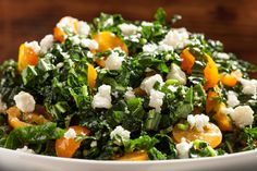 This salad recipe tosses ribbons of kale with cherry tomatoes, feta cheese, scallions, and mint in a tangy Dijon-garlic dressing.