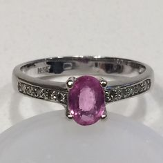 Pink sapphire and diamond 14k white gold ring  14k white gold with genuine pink sapphire surrounded by diamonds.  2.5 grams gold ** Diamonds: cut round; clarity I2-I3; color J-K; carats .05 total weight ** Sapphire cut oval; length 6mm; height 4mm. Jewelry Rings