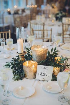 greenery centerpiece with gold votives and calligraphy table number