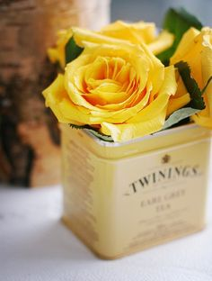 Yellow roses in tea tin. My kind of flower display :-)