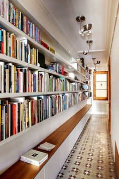 The architects had always wanted a library but didn't have the space, so they took advantage of the wide hallway to install bespoke shelves they designed themselves. The lower cupboards are used for storage.