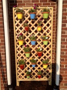 Hang colorful flower pots on a trellis using hangapot. the hidden hanger! You don't need the trellis.you can hang them on the brick! Hanging Potted Plants, Hanging Herbs, Hanging Flower Pots, Patio Plants, House Plants, Patio Pictures, Hang Pictures, Herb Wall, Large Backyard Landscaping