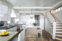 Well appointed kitchen features a gray wash center island accented with a white quartz countertop fitted with a sink and seating backless gray barstools on rustic wood floors  illuminated by three white enamel industrial pendants hung from a white plank ceiling.