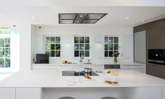 Above the central island a flush-fit Gaggenau ceiling extractor removes unwanted cooking odours. A barstool seating arrangement allows the cook to converse with guests whilst working or space to share a coffee. Kitchen Extractor, Central Island, Central Kitchen, Bathroom Bath, Kitchen Images, Luxury Kitchens, Bathroom Interior, Modern Classic, Case Study