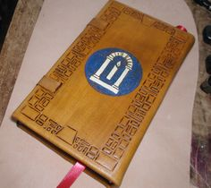 An eighty page hand-bound leather covered and tooled journal, two were made for prizes for the Rose Tourney held in Brendoaken April 30th.  This is the back bearing the A&S Symbol tooled into the leather covering and painted.