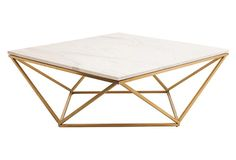White marble rests on a geometric stainless-steel base, forming an eye-catching, contemporary coffee table.