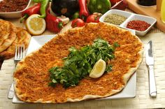"""Lahmacun — A pizza like dish with a topping of finely minced meat and onions with spices on flaky thin dough. It is served with tomatoes, lettuce, parsley or rocket and most people prefer to squeeze lemon on it and roll to eat easier like tacos. It originates from the early Syrian cuisine of the Levant and the name comes from Arabic """"dough with meat"""". It has been a popular fast food like dish in Turkey."""