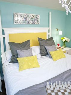 A Bright White And Yellow Four Poster Bed Pops Against The Robins Egg Blue  Walls In This Bedroom. HGTVu0027s Design On A Dime Designer Casey Noble Uses  Simple ...
