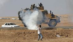 A protester throws stones at an armoured army vehicle during a pro-Kurdish demonstration in solidarity with people of Kobani, near the Mursitpinar border crossing on the Turkish-Syrian border, in the Turkish town of Suruc in southeastern Sanliurfa province October 7, 2014. Islamic State fighters advanced into the south west of the Syrian Kurdish town of Kobani overnight, a monitoring group said on Tuesday, taking several buildings to gain attacking positions from two sides of the city.