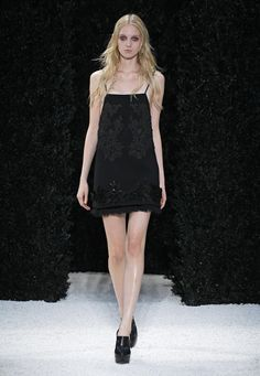 LOOK 8 Black wool twill bib neck mini shift dress with passementiere embellishment, fabric covered sequin flowers and ruffled hem.
