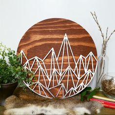 Super modern hand designed geometric mountains placed upon a hand cut circular wood piece stained with American Walnut. Sweet accents of