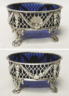 An elegant pair of antique sterling silver salts of oval form with pretty pierced decoration with swags. Blue glass liners. Lovely classical style with bead borders and standing on pierced shaped feet. To the front there is a hand engraved crest within a shield. Owners initials underneath. Weight of silver 105 grams, 3.3 troy ounces. Height 5 cms. Top measures 8.5 x 6.25 cms. Sheffield 1777. Maker Fenton, Creswick & Co.
