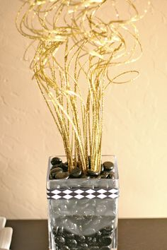 Centerpiece with colored stones or beads to reflect the Gatsby theme. Just another center piece idea if feathers rub you the wrong way.