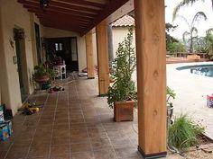 wrap around porch, tile cut concrete, wooden beams